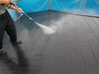 洗浄した塗膜などがまわりに舞わないようていねいにビニール養生を行い、屋根に蓄積した汚れもこそげ落としていきます。